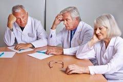 Médecins inquiétés pensant lors de la réunion Image stock