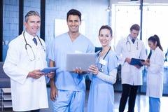 Médecins à l'aide de l'ordinateur portable et du comprimé numérique regardant l'appareil-photo Images stock