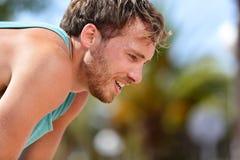 Müder erschöpfter Mannläufer, der nach Training schwitzt Stockbilder