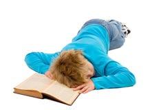 Müder gefallenes schlafendes des Jugendlichen Junge auf seinem Buch Lizenzfreie Stockfotografie