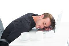 Müder Geschäftsmann, der auf Laptop schläft Stockbild
