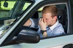 Müdes Geschäftsmannautofahren Stockfoto