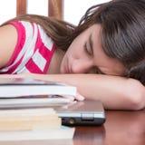 Müdes Mädchen, das auf dem Tisch über ihrem Laptop mit einem Stapel Büchern schläft Stockbilder