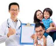 Médico de sexo masculino chino y familia paciente joven Imágenes de archivo libres de regalías
