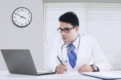 Médico de sexo masculino con el cuaderno en oficina Foto de archivo libre de regalías