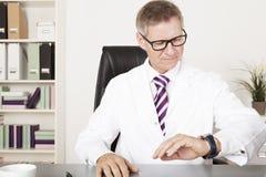 Médico de sexo masculino Watching Wrist Watch Imagen de archivo libre de regalías