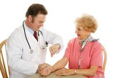 Médico mayor - verificación del pulso Imagen de archivo