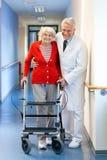 Médico que ayuda a una mujer mayor en un caminante Imágenes de archivo libres de regalías