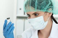Médico que mira el pequeño frasco con el líquido Foto de archivo libre de regalías