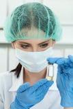 Médico que mira el pequeño frasco con el líquido en laboratorio Fotografía de archivo libre de regalías