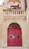 Mdina details. MDINA, MALTA - SEPTEMBER 15, 2015: Mdina architecture details - red door and balcony, windows with red window shutters and Maltese cross inside Stock Photos