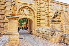 Mdina Gate and entrance in old fortified city Malta. Mdina, Malta - April 4, 2014: Mdina Gate and entrance in the old fortified city, Malta. People on the Stock Image