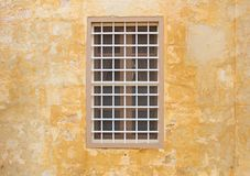 Malta, Mdina. Window on a yellow wall in the old medieval city. Mdina, Malta island. Window with metal bars on a yellow wall in the old medieval city Stock Images