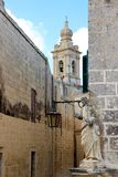 Mdina, Malta, July 2014. View of the bell tower of the Catholic Cathedral and the statue of the Holy Apostle. stock image