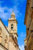 Mdina, Malta. Narrow street wth church belfry and buildings stone facades on blue sky background Royalty Free Stock Photo