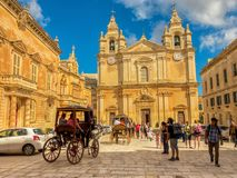 Mdina, Malta, October 7, 2017: picturesque horse carriage and to. Urists on catholic St. Peter & Paul Cathedral Stock Images
