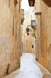 Mdina narrow street. Narrow medieval stone paved street in Mdina the former capital of Malta Royalty Free Stock Images