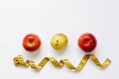 Meça as maçãs da fita e dos frutos frescos, pera no fundo branco Peso da perda, corpo magro, conceito da dieta saudável fotografia de stock