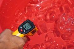 Meça como o frio o gelo na água é Fotos de Stock