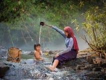Mãe asiática que rega a filha Imagem de Stock Royalty Free