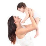 Mãe bonita que aumenta sua filha que olha com ternura Fotografia de Stock Royalty Free