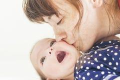 Mãe caucasiano feliz que beija sua criança pequena recém-nascida Imagens de Stock Royalty Free