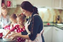 Mãe com as crianças na cozinha Fotos de Stock Royalty Free