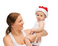Mãe com o bebê no chapéu do ajudante de Santa Fotografia de Stock