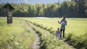 Mãe com suas bolhas de sabão de sopro da criança na natureza Fotografia de Stock