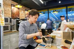 With Me convenience store. SEOUL, SOUTH KOREA - CIRCA MAY, 2017: worker at a convenience store in Seoul stock photography