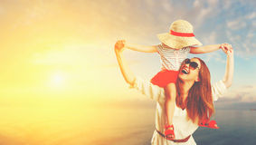 Mãe da família e filha felizes da criança na praia no por do sol Imagem de Stock