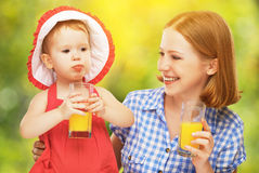 Mãe da família e suco de laranja bebendo da filha do bebê na soma Imagem de Stock