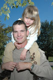 Me and Dad. A father and child spend time at the park. Father giving his daughter a ride on his shoulders stock photo