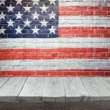 4ème du fond de juillet avec la table en bois au-dessus du drapeau des Etats-Unis peint sur le mur de briques Image libre de droits