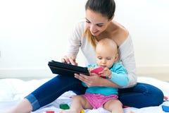 Mãe e bebê que usa a tabuleta digital em casa Imagens de Stock