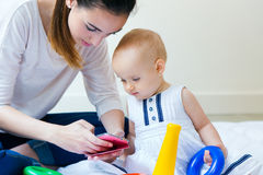 Mãe e bebê que usa um smartphone em casa Fotografia de Stock Royalty Free