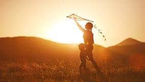 A mãe e a criança felizes da família correm no prado com um papagaio no summe Foto de Stock