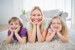 Mãe e crianças com cabeça nas mãos que encontram-se no tapete Fotos de Stock Royalty Free