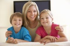 Mãe e crianças que olham a tevê do tela panorâmico em casa Fotografia de Stock