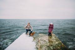Mãe e filha com seu cão de estimação pequeno que andam no cais velho Feriados de inverno, fundo do mar Fotos de Stock