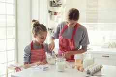 A mãe e a filha estão cozinhando Foto de Stock Royalty Free