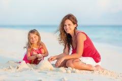 A mãe e a filha pequena jogam na praia Fotos de Stock