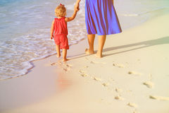 Mãe e filha que andam na praia que deixa a pegada na areia Foto de Stock
