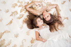 Mãe e filha que encontram-se no assoalho no dres brancos bonitos Fotografia de Stock