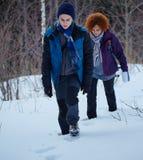 Mãe e filho que andam através da neve Fotografia de Stock