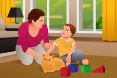 Mãe e filho que jogam com um gato em casa Fotografia de Stock Royalty Free
