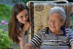 Me e la nonna, ragazza sorprendono la sua grande-nonna immagine stock