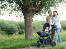 Mãe e pai que andam fora e que empurram o bebê no pram Imagens de Stock