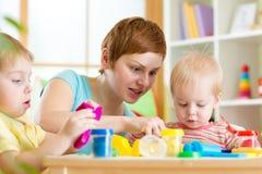 A mãe ensina-lhe crianças trabalhar com playdough colorido Fotos de Stock