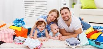 A mãe feliz da família, o pai e duas crianças embalaram as malas de viagem FO Imagem de Stock